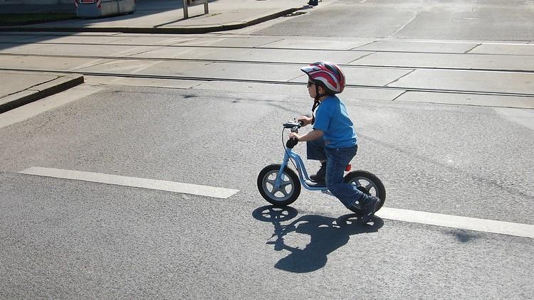Kind fährt mit einem Laufrad auf der Straße